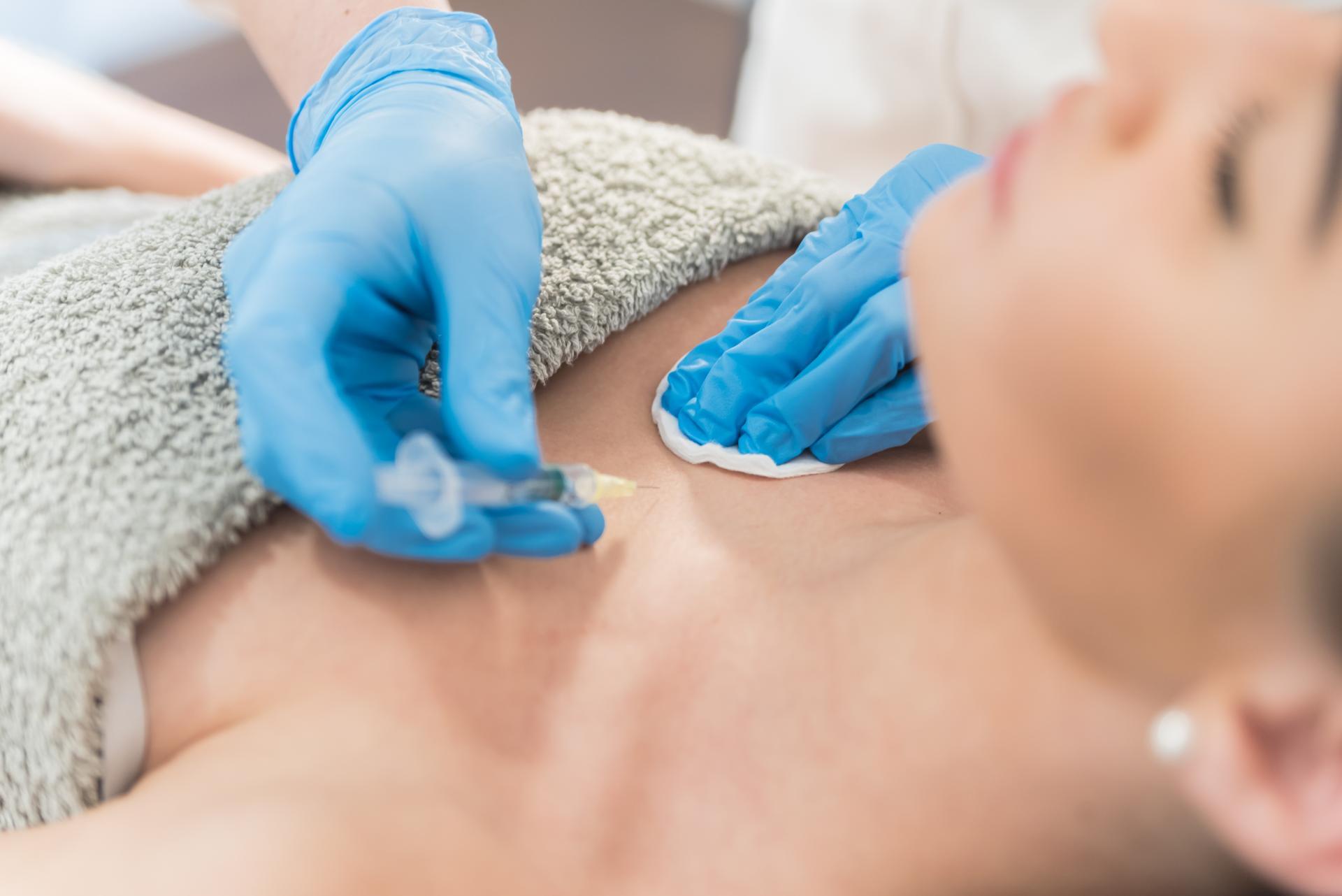 medico aplicando tratamiento inyección en escote de mujer