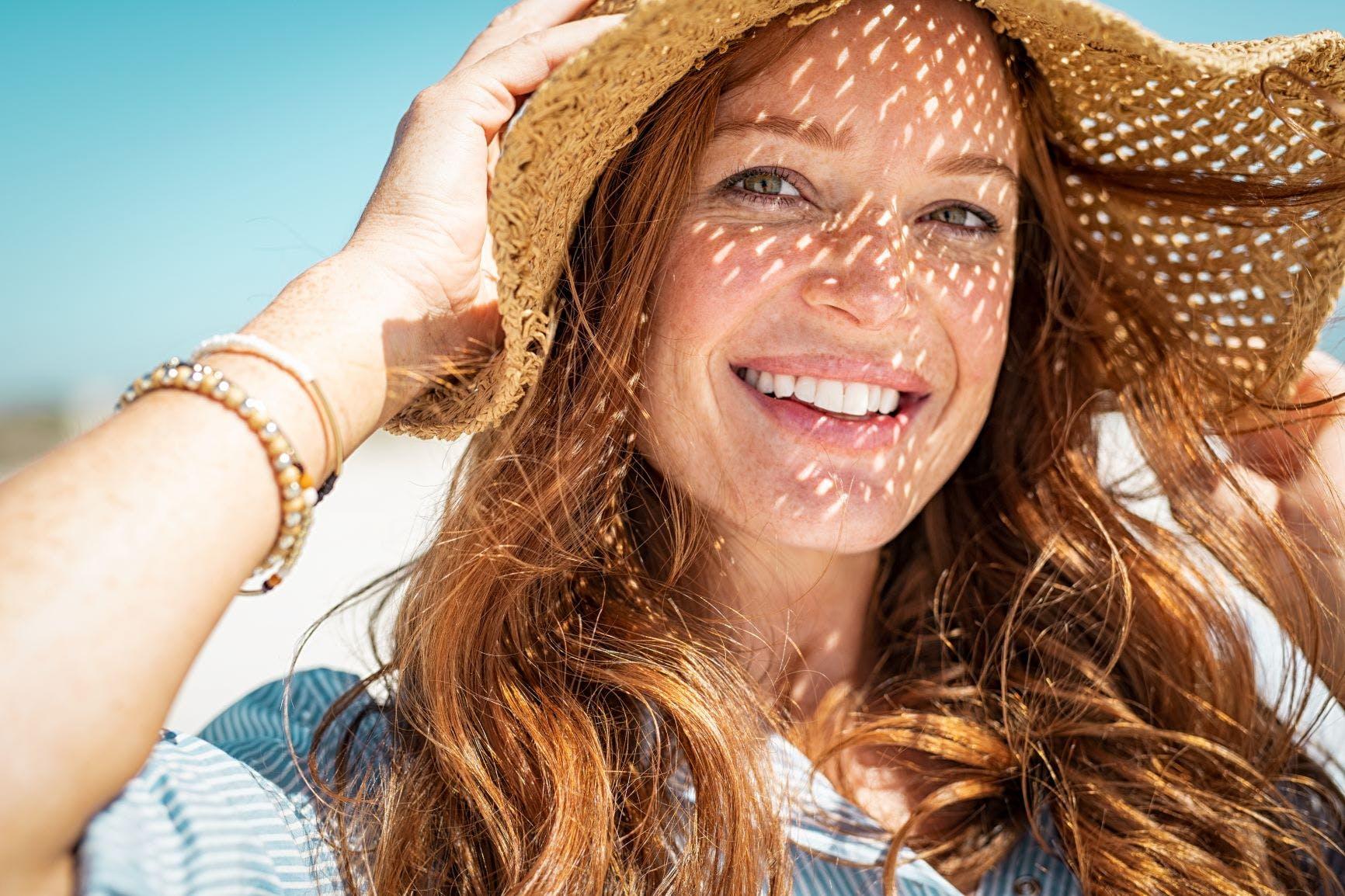 mujer sonriendo con sobrero al sol